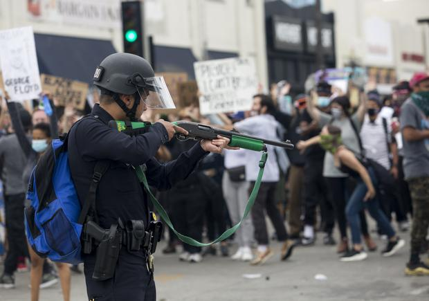 A police officer prepares to fire rubber bullets during a protest in Los Angeles (Ringo HW Chiu/AP)