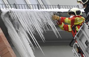 Firefighters break large icicles from the gutter of a house in the German city of Erfurt (Martin Schutt/dpa via AP)