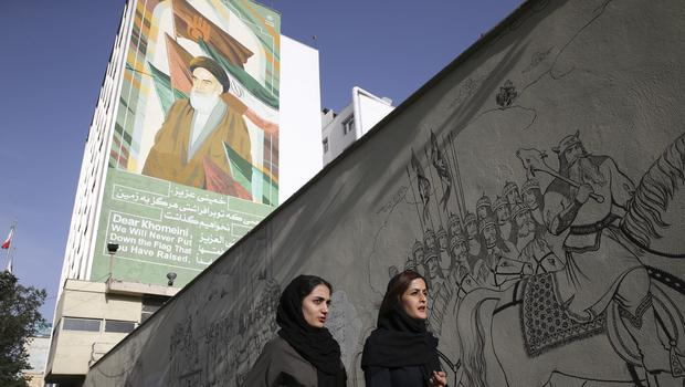 Iranian women walk past a portrait of the late revolutionary founder Ayatollah Khomeini and paintings of Persian poetry in Tehran (AP)