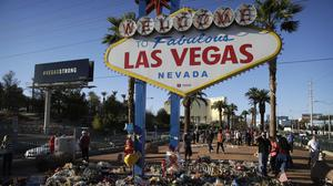 Flowers and candles surround the famous Las Vegas sign at a makeshift memorial for victims of the mass shooting (AP)