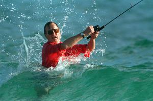 Then-president-elect George HW Bush casts a line while fishing in Gulf Stream, Florida (AP Photo/Kathy Willens, File)