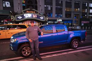 Steve Cruz poses with his Chevy Colorado in Times Square (Mark Lennihan/AP)