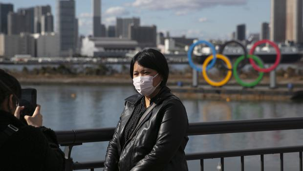 FILE – In this Jan. 29, 2020, file photo, a tourist wearing a mask poses for a photo with the Olympic rings in the background, at Tokyo's Odaiba district. Tokyo Olympic organizers repeated their message at the start of two days of meetings with the IOC: this summer's games will not be cancelled or postponed by the coronavirus spreading neighboring China. (AP Photo/Jae C. Hong, File)