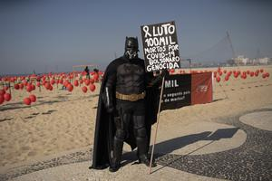 A man dressed in a Batman costume holds a sign with a message that reads in Portuguese 'Mourning 100,000 deaths of Covid-19, Bolsonaro genocide' (Silvia Izquierdo/AP)