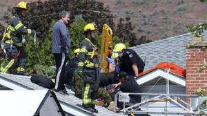 First responders attend to a person on a rooftop at the scene of a crash involving a Canadian Forces Snowbirds airplane in Kamloops, British Columbia (Brendan Kergin/Castanet Kamloops/The Canadian Press via AP)