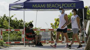 People wearing protective face masks walk past a closed entrance to a beach in Florida (Lynne Sladky/AP)