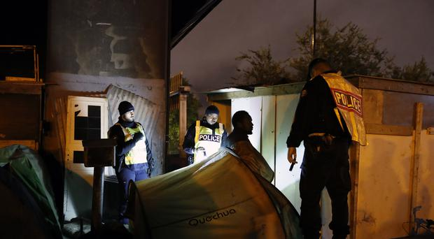 French Police officers move a migrant during a large operation to dismantle makeshift camps (Francois Mori/AP)