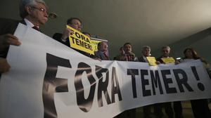 """Politicians hold a banner saying: """"Temer Out"""" (AP)"""