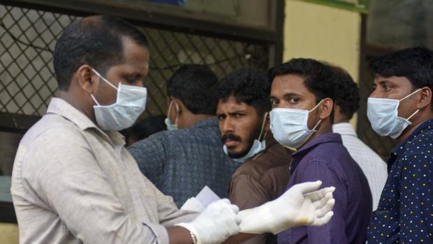 People wait outside a hospital wear masks as a precautionary measure against the Nipah virus at the Government Medical College hospital in Kozhikode (AP)