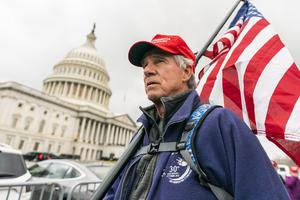 Lloyd Watkins, of Nashville, Tennessee, a supporter of President Donald Trump, carries a flag outside the Capitol in Washington (Manuel Balce Ceneta/AP)