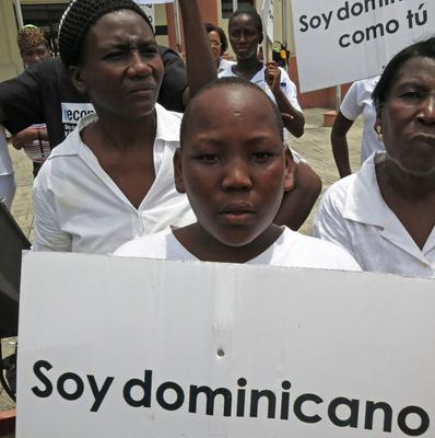 "A youth of Haitian descent holds a sign that reads in Spanish ""I'm Dominican"" during a protest in Santo Domingo, Dominican Republic (AP/Ezequiel Abiu Lopez)"