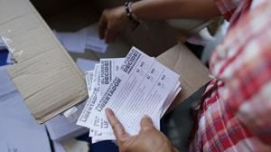 Volunteers count the ballots after the poll station closed during a symbolic referendum in Caracas, Venezuela (AP)