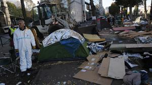 Workers clean a migrant camp after a police operation in Paris (AP)