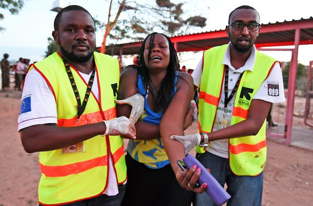 Paramedics help a woman who was injured during the attack on the campus yesterday