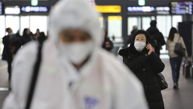 A woman wears a mask as an employee works to prevent a new coronavirus at Suseo Station in Seoul, South Korea (Ahn Young-joon/AP)