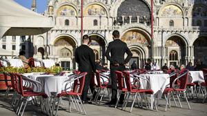 Waiters with no customers in St Mark's Square in Venice, Italy (Claudio Furlan/Lapresse/AP)