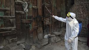 A volunteer in a protective suit sprays disinfectant on storefronts to help curb the spread of the coronavirus in Kabul, Afghanistan, Sunday, March 29, 2020. The government Friday ordered a three-week lock-down for Kabul to stem the spread of the new coronavirus. (AP Photo/Rahmat Gul)