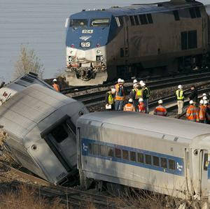 An Amtrak train travelling on an unaffected track, passes the derailed commuter train (AP)
