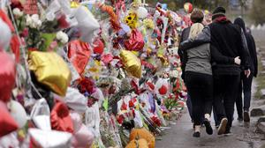 People walk past a memorial outside the school for victims following the deadly shooting there (AP)