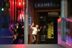 Hostages leave the building with their arms raised