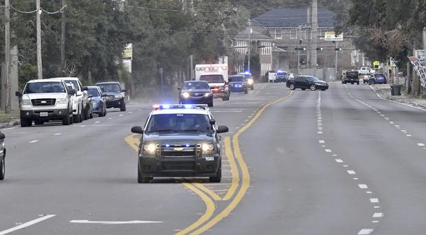 Police cars escort an ambulance after a shooter opened fire inside the Pensacola Air Base (Tony Giberson/ Pensacola News Journal via AP)