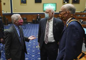 Dr Fauci speaks with Dr Robert Redfield (centre), director of the Centres for Disease Control and Prevention, after testifying (Kevin Dietsch/Pool/AP)