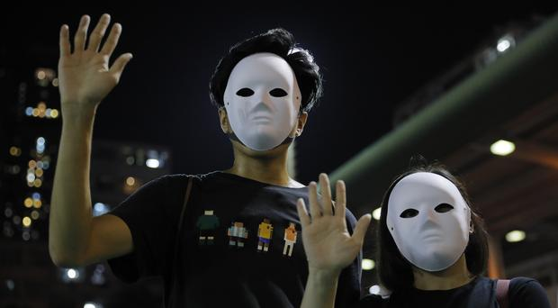 Protesters defied the ban on wearing masks on Saturday (Kin Cheung/AP)