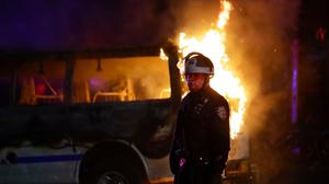 A police officer walks past a burning police vehicle on DeKalb Avenue in the Brooklyn borough of New York (Frank Franklin II/AP)
