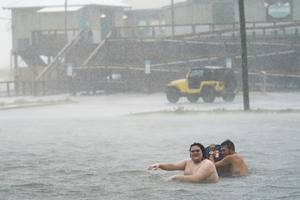 People play in a flooded car park in Pensacola Beach, Florida (Gerald Herbert/AP)