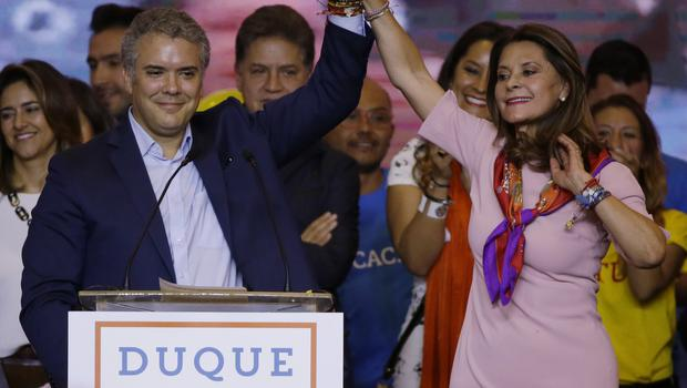 Ivan Duque and his vice presidential formula Marta Lucia Ramirez raise arms after winning the first round of the presidential election (AP Photo/Fernando Vergara)