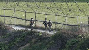 South Korean army soldiers patrol along the barbed-wire fence in Paju, South Korea, near the border with North Korea, (Ahn Young-joon/AP)