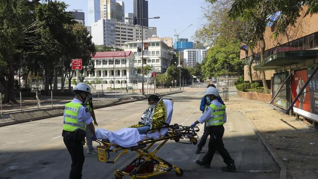 A protester is wheeled on a stretcher by first aid personnel (VIncent Thian/AP)