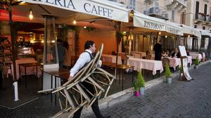 Waiters pile up chairs and prepare to close at a restaurant in Rome (AP/Andrew Medichini)