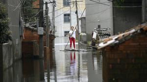 A woman pushes a makeshift raft down a flooded alleyway in a village in Yongxiu in central eastern China's Jiangxi province (Chinatopix via AP)