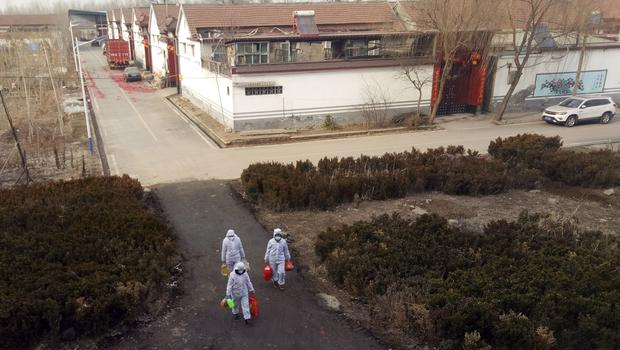 Government workers in protective suits carry groceries for a family under home quarantine in Zouping in eastern China's Shandong Province (Chinatopix/AP)