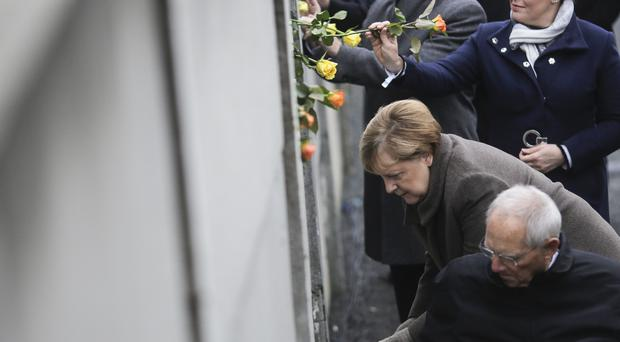German chancellor Angela Merkel and ministerial colleagues place their own tributes at the wall (Markus Schreiber/AP)