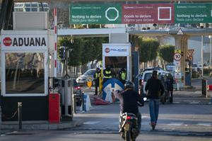 Spanish police officers stand at the border as people enter Gibraltar from the neighbouring Spanish city of La Linea (Emilio Morenatti/AP)