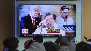 People watch a TV screen showing images of North Korean leader Kim Jong Un, South Korean President Moon Jae-in and US President Donald Trump (Ahn Young-joon/AP)