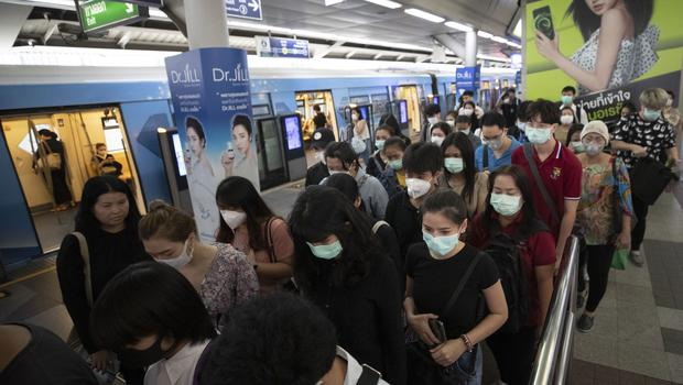 As the number of cases of coronavirus worldwide continues to rise, commuters at a subway station in Bangkok wear facemasks as protection against the disease (Sakchai Lalit/AP)