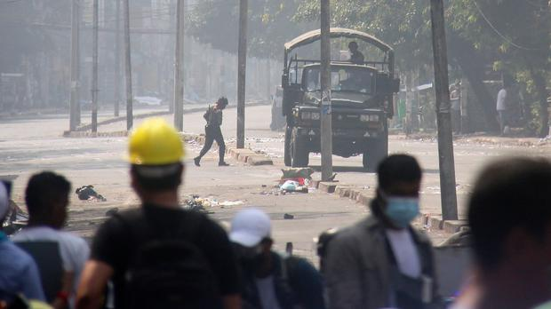 Protesters check a police truck's movement during an anti-coup protest on a blocked road in Yangon, Myanmar, Tuesday, March 2, 2021. Demonstrators in Myanmar took to the streets again on Tuesday to protest last month's seizure of power by the military, as foreign ministers from Southeast Asian countries prepared to meet to discuss the political crisis. (AP Photo)