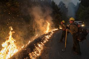 Firefighters monitor a controlled burn in California (Nic Coury/AP)