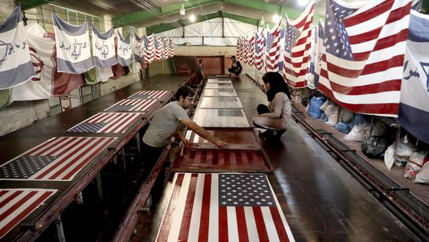 Workers in Iran print US flags (Ebrahim Noroozi/AP)