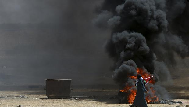 A Palestinian woman walks past burning tyres near the Israeli border fence, east of Khan Younis (AP)