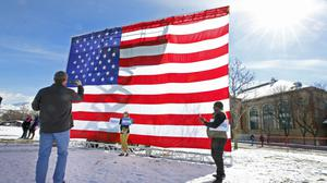 Supporters of Democratic presidential candidate Bernie Sanders take pictures in front of a large US flag before a rally Monday, March 2, 2020, in Salt Lake City (AP)