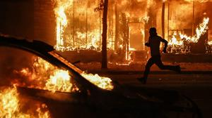 A protester runs past burning cars and buildings in St. Paul, Minnesota ((John Minchillo/AP)