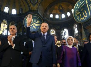 Turkey's President Recep Tayyip Erdogan, centre, accompanied by his wife Emine, right, waves to supporters as he walks in the Hagia Sophia (Kayhan Ozer/AP)