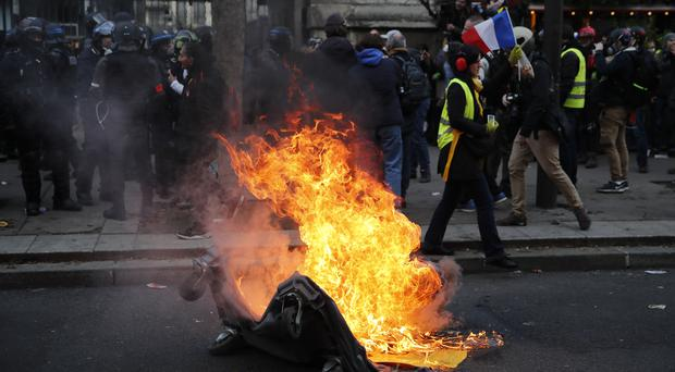 A rubbish bin set on fire by protesters in a demonstration against planned pension reforms (Francois Mori/AP)