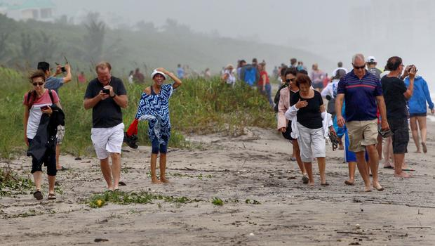 People walk the shoreline of Juno Beach under high gust winds as Hurricane Dorian crawls towards Florida (Carl Juste/Miami Herald via AP)