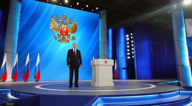 Vladimir Putin listens to the national anthem after his speech to the State Council (Mikhail Klimentyev/AP)