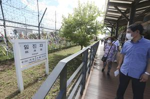 People wearing face masks pass a sign showing the distance to North Korea's city Kaesong and South Korea's capital Seoul at the Imjingak Pavilion in Paju, near the border with North Korea (Ahn Young-joon/AP)